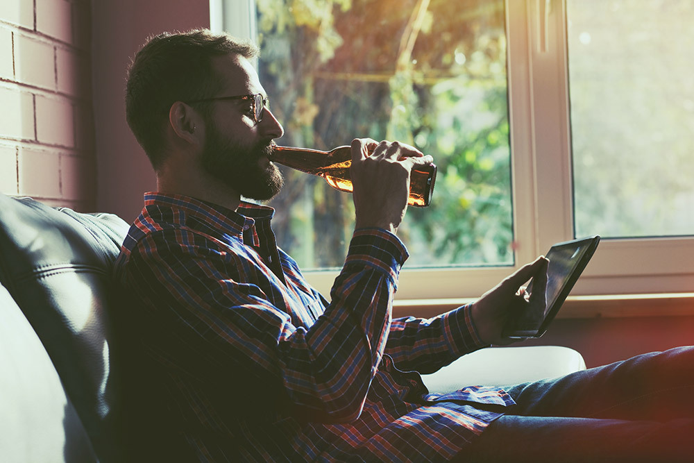 Image of person drinking a beer whilst using a tablet device